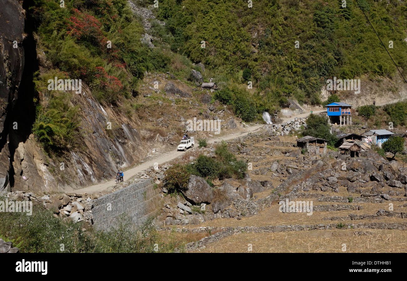 Jeep and people walking on the Annapurna road in the Gorkha region of Nepal. - Stock Image