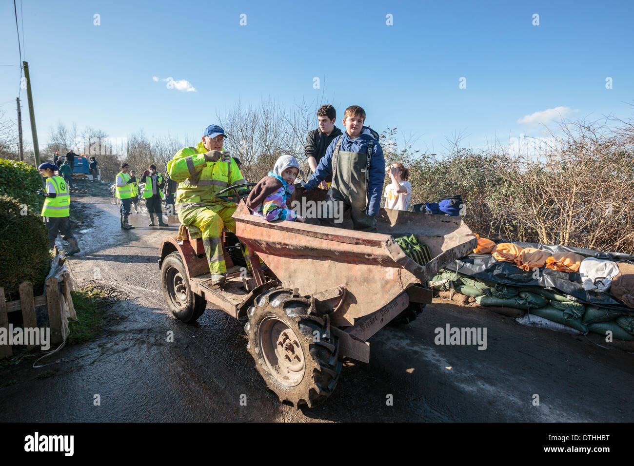 Volunteer aid workers help distribute supplies in the flooded village of Moorland on the Somerset Levels. - Stock Image