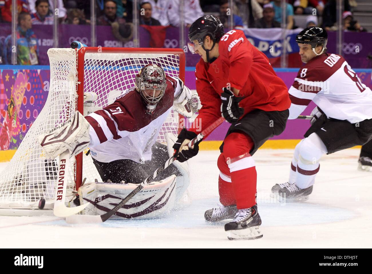 Sochi, Russia. 18th Feb, 2014. Mens ice skating playoffs. Switzerland versus Latvia. Torhueter Edgars Masalskis (L) and Sandis Ozolins (LAT) challenges Damien Brunner (SUI) Credit:  Action Plus Sports/Alamy Live News - Stock Image