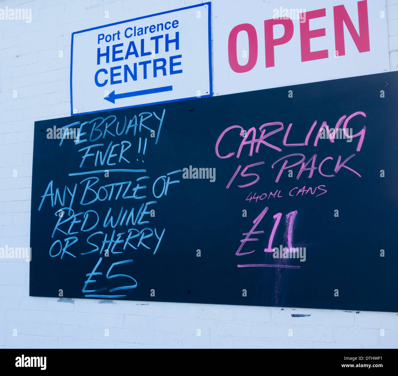 Alcohol prices on blackboard outside shop with Health centre sign above blackboard - Stock Image