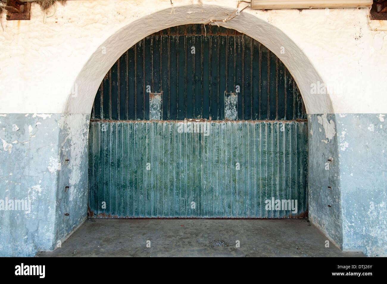arched doorway with old metal doors - Stock Image
