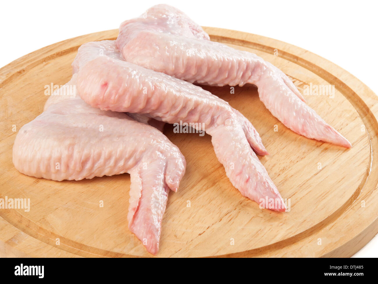 Damp hen wings on the cutting board. - Stock Image