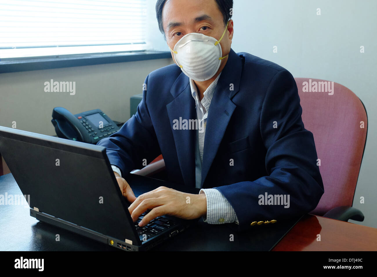 Asian man wearing a face mask inside office due to air pollution - Stock Image