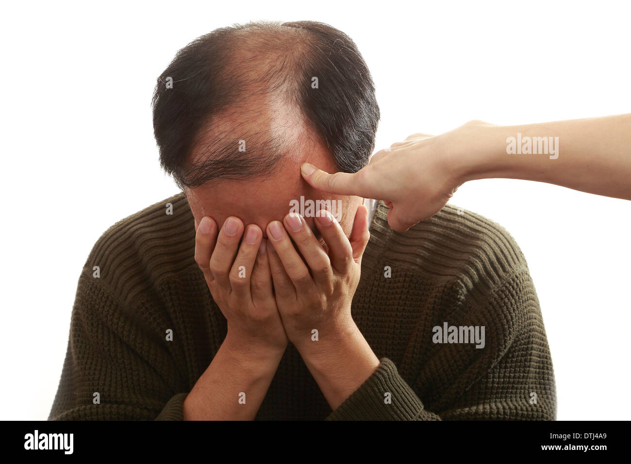 A shameful asian man covering his face with both hands - Stock Image