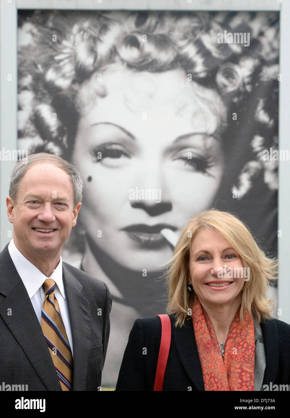 US ambassador John Bonell Emerson in Germany and his wife Kimberly Marteau Emerson stand in front of a placat of German actress Marlene Dietrich at the Babelsberg Studios in Berlin, Germany 19 February 2014. The diplomat visitied the media location together with the Premier of Brandenburg during his first courtesy call in Brandenburg. The ambassador informed himself about US film productions which were realized in Babelsberg. Photo: RALF HIRSCHBERGER/dpa - Stock Image