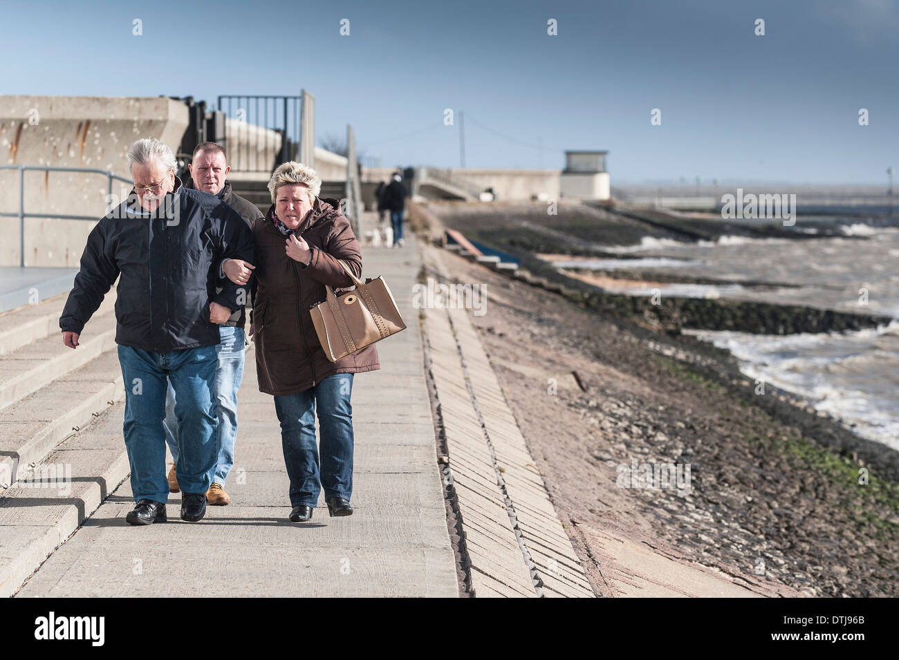 People walking against the wind on the sea wall at Canvey Island in Essex. - Stock Image