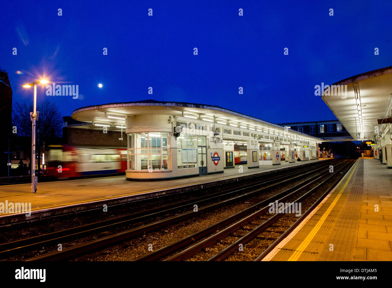 Full moon over East Finchley art deco tube station night - Stock Image