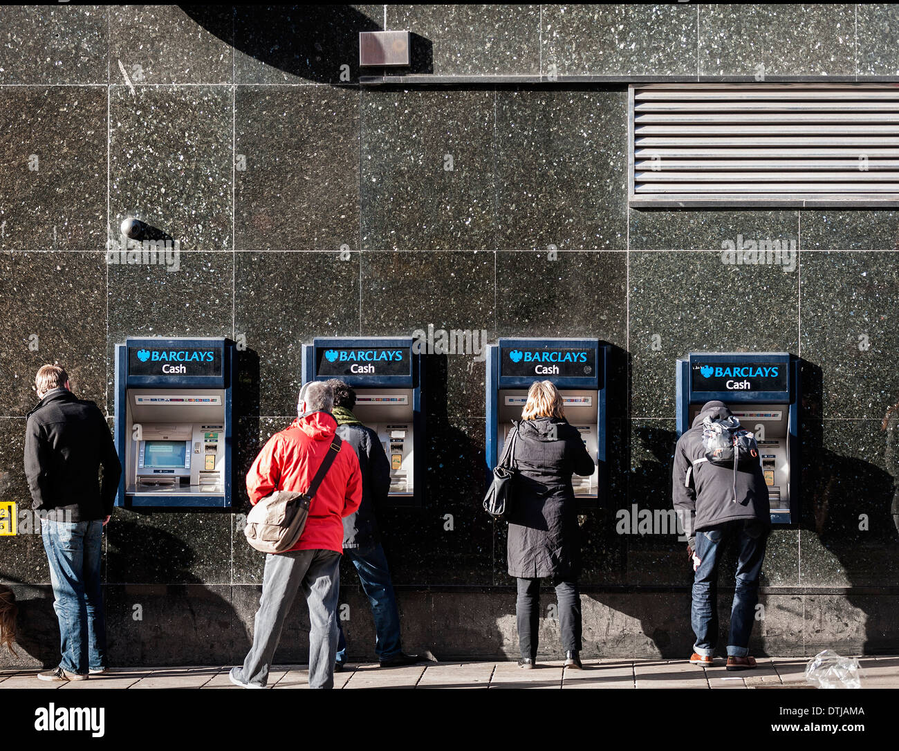 Customers withdrawing money from Barclays ATM. - Stock Image