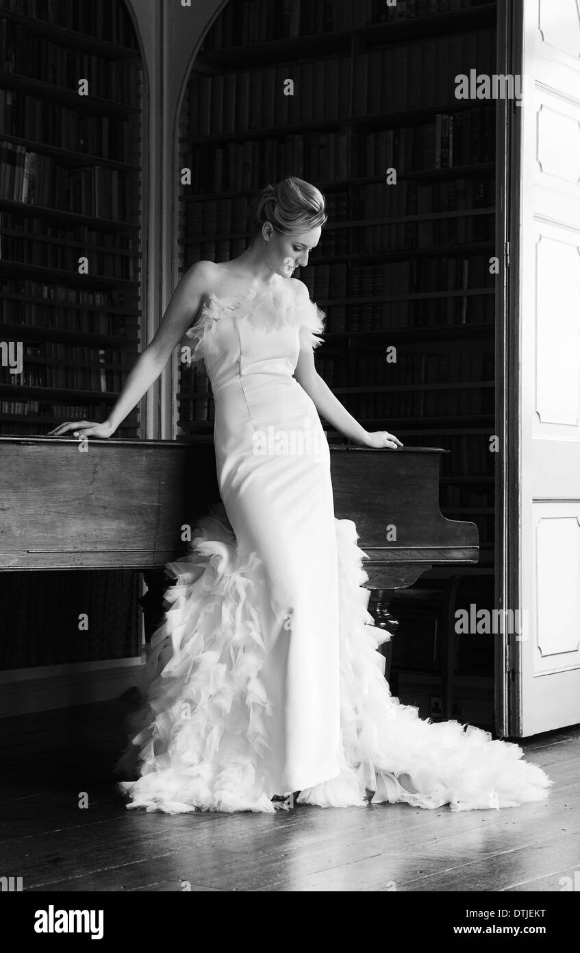 A woman wearing an elegant floor length gown with a full skirt decorated with feathers England - Stock Image