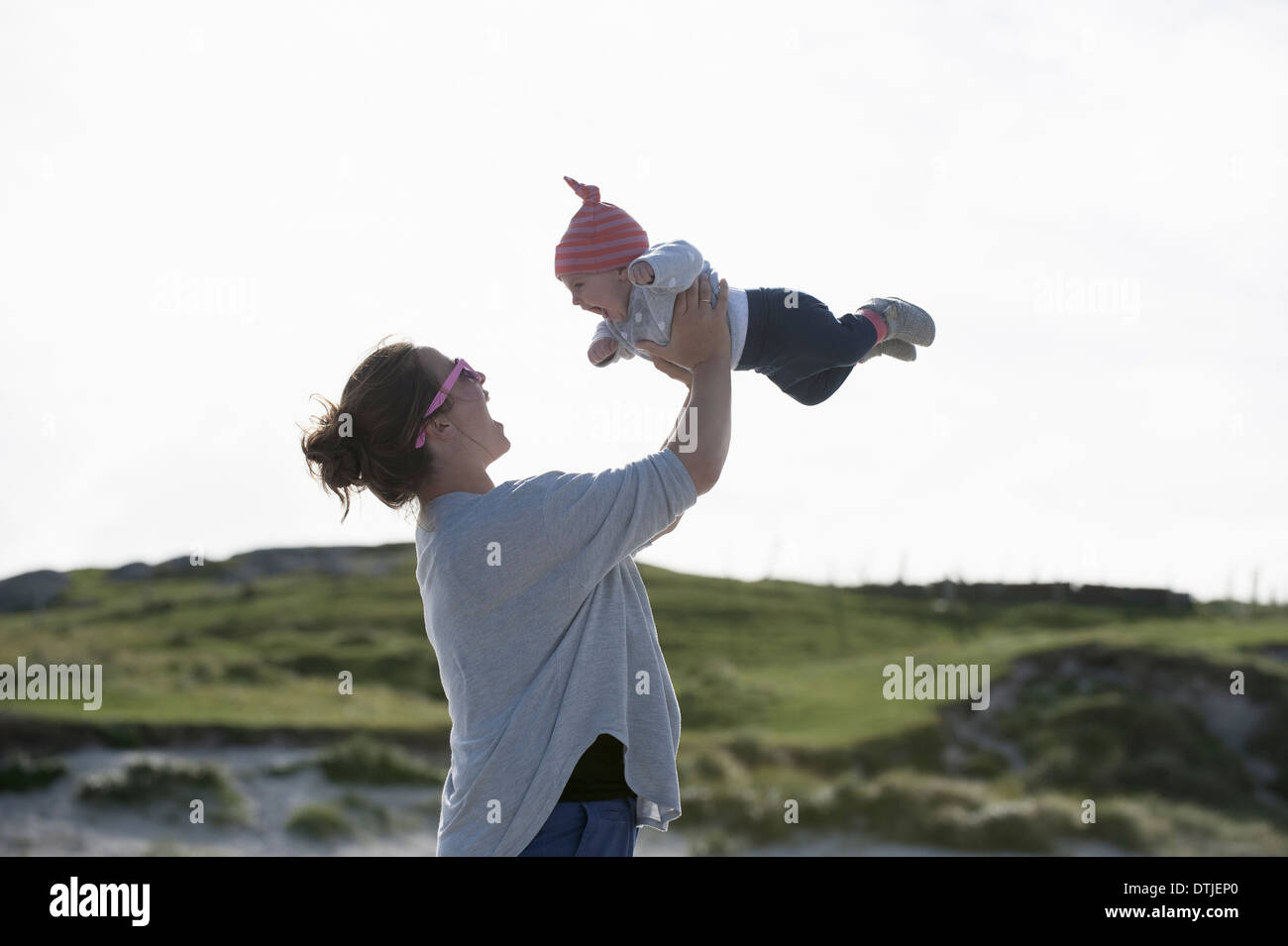 A mother raising her baby in the air At the seaside England - Stock Image