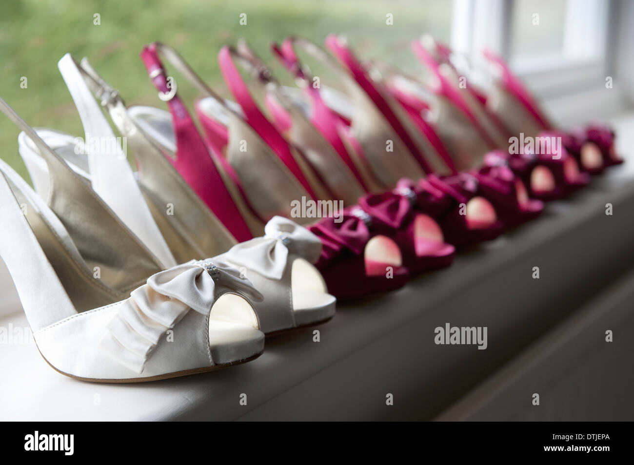 A row of high heeled shoes Pairs of peep toe slingbacks in white and pink  Special occasion  England - Stock Image