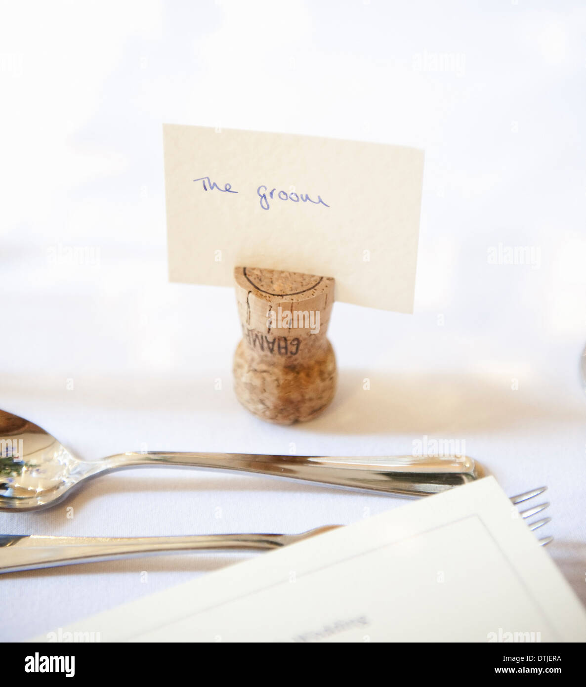 Top table at a wedding banquet An upside down cork with name tag for the groom Silver fork and spoon England - Stock Image