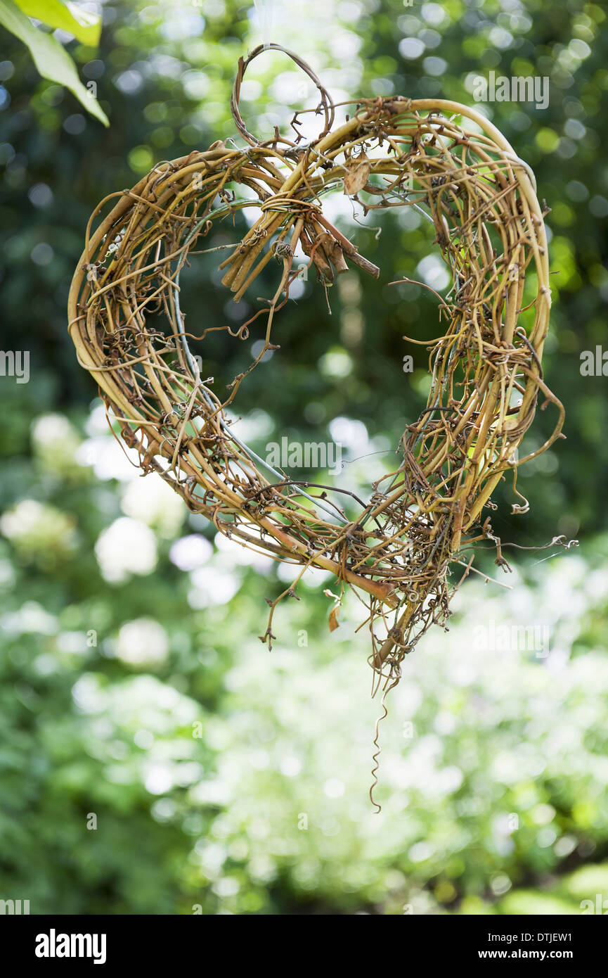 A heart shape made out of woven twigs hanging from a tree Simple decorations  England - Stock Image