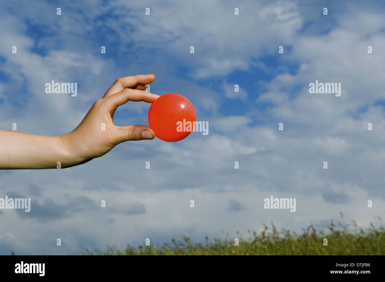 A person's outstretched hand holding a red ball Gloucestershire England Stock Photo