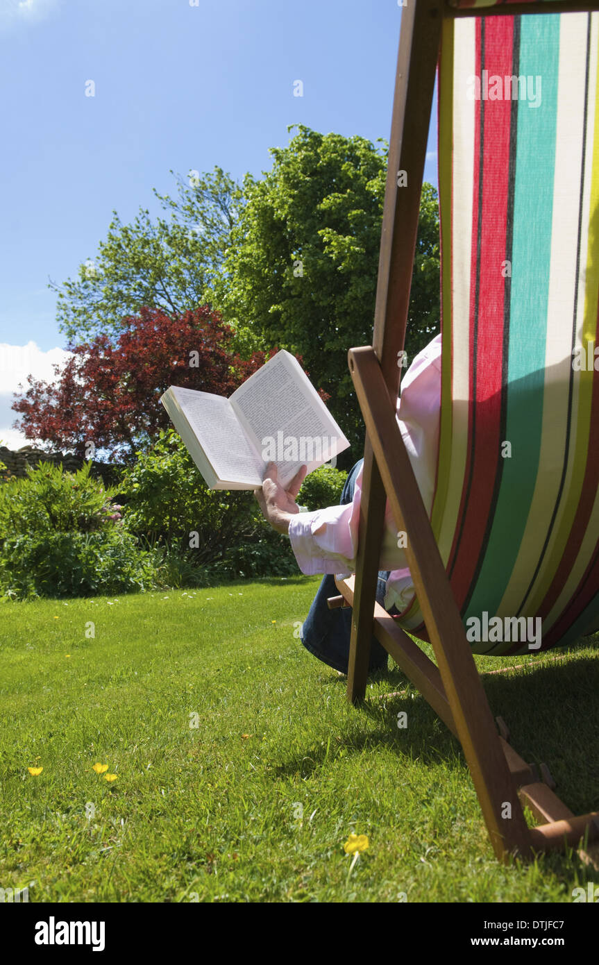 A person sitting in a deckchair reading Gloucestershire England Stock Photo