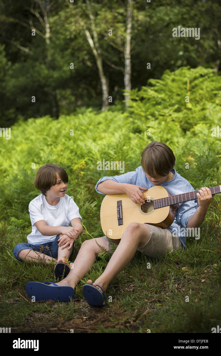 Two boys camping in New Forest Sitting on the grass one playing a guitar  Hampshire England - Stock Image