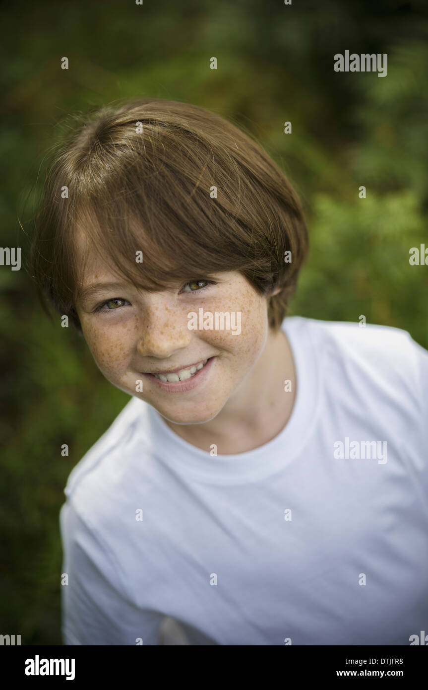 A boy in a white tee-shirt looking up at the camera  Hampshire England - Stock Image