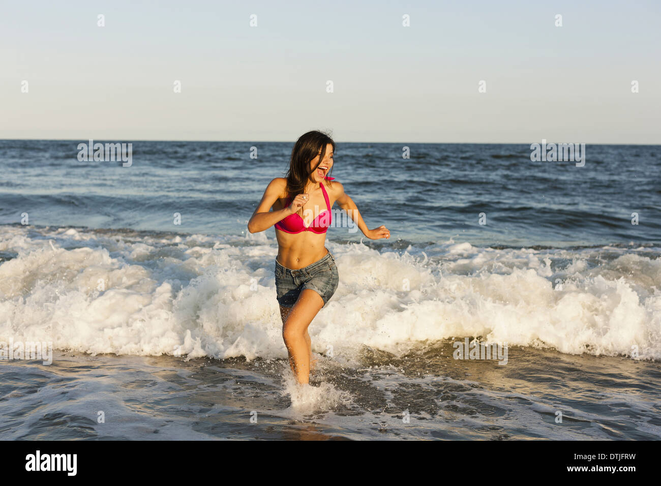 A beautiful young women at the water's edge on the beach in Atlantic City New Jersey USA - Stock Image