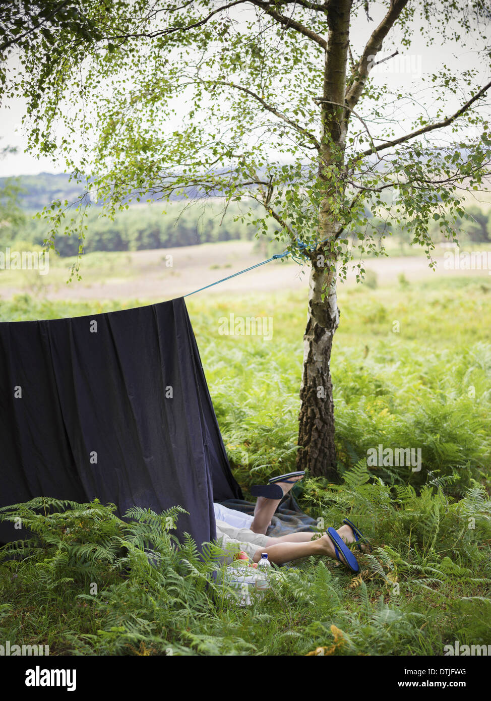 Two boys camping in the New Forest lying under a canvas shelter Hampshire England - Stock Image