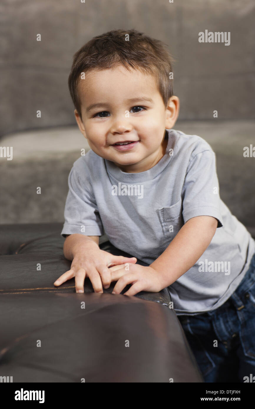 A child leaning on a brown chair looking at the camera smiling  Pennsylvania USA - Stock Image