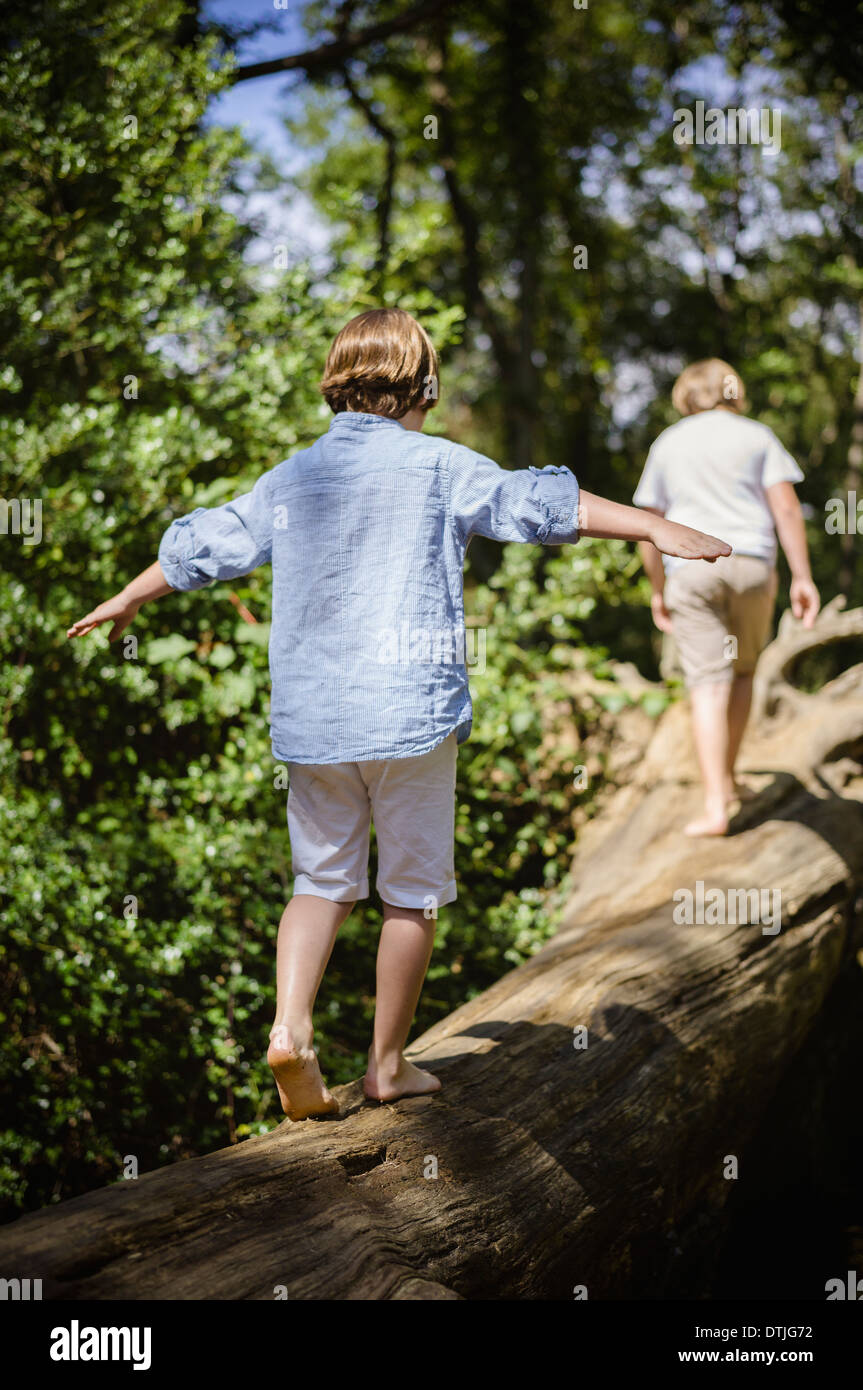 Two boys camping in the New Forest Walking along a log above the water balancing with their arms outstretched  Hampshire Stock Photo