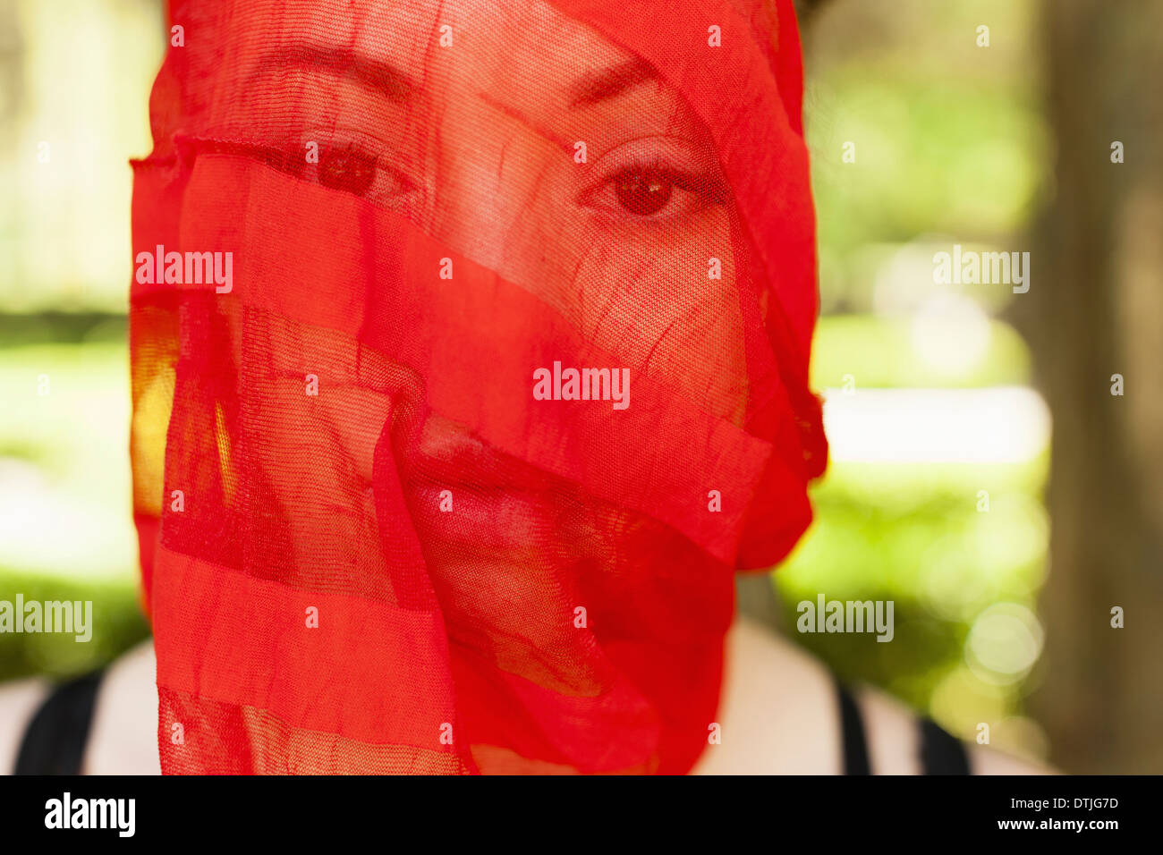 A young woman with a red seethrough sheer veil across her face Pennsylvania USA - Stock Image