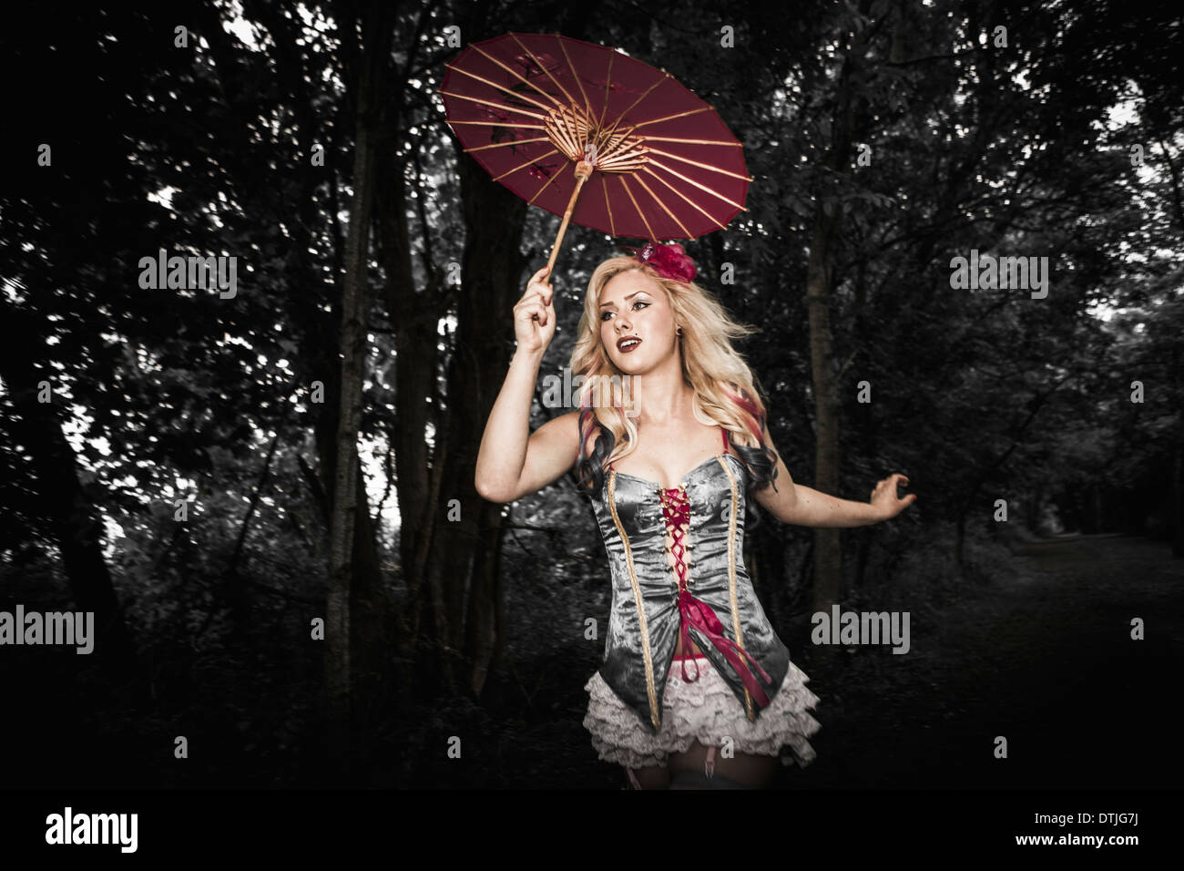 A woman wearing a laced basque, striped stockings and suspenders Holding a paper sunshade umbrella A carnival circus outfit - Stock Image