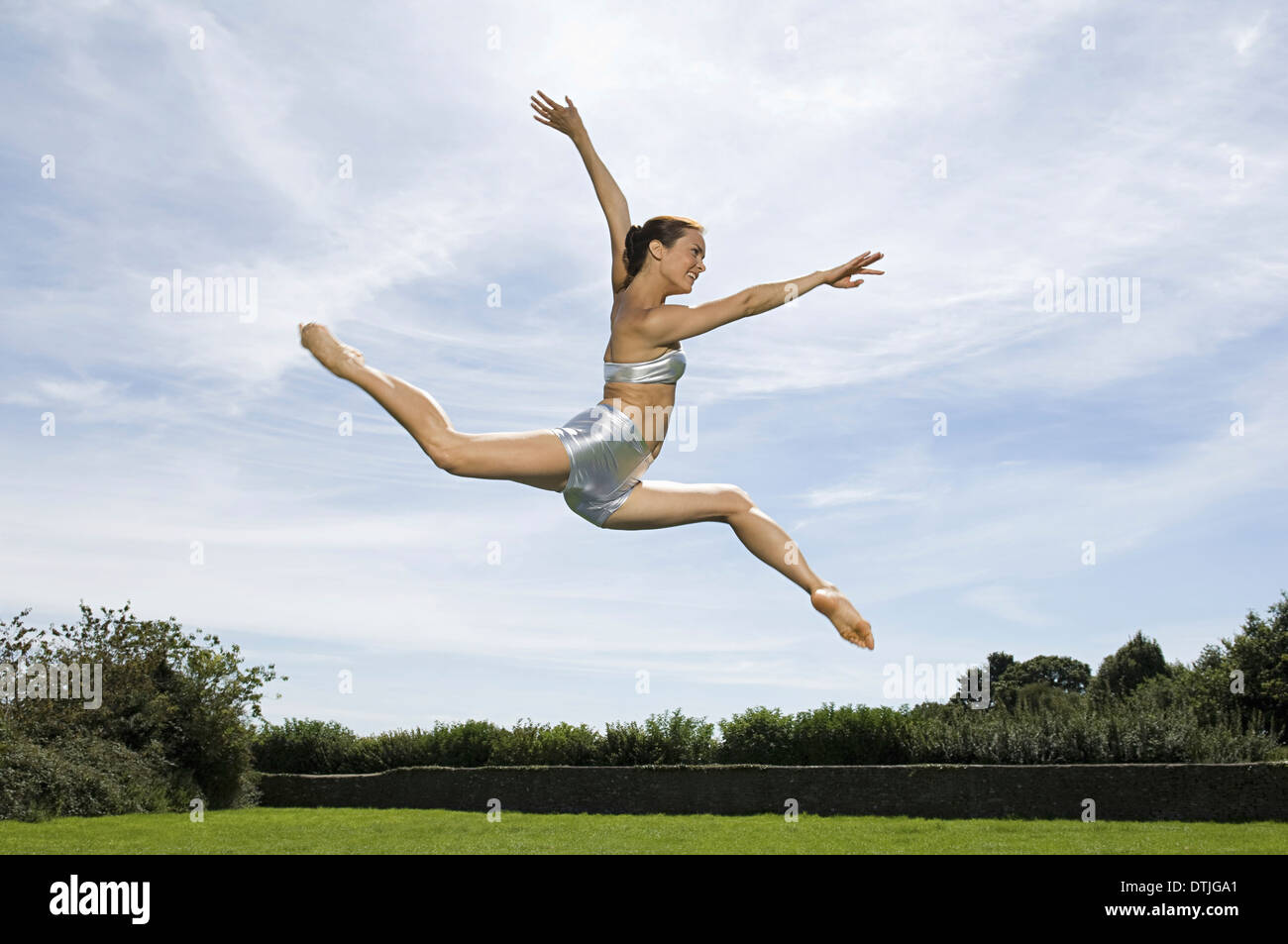 A young woman leaping in the air Acrobat  England - Stock Image