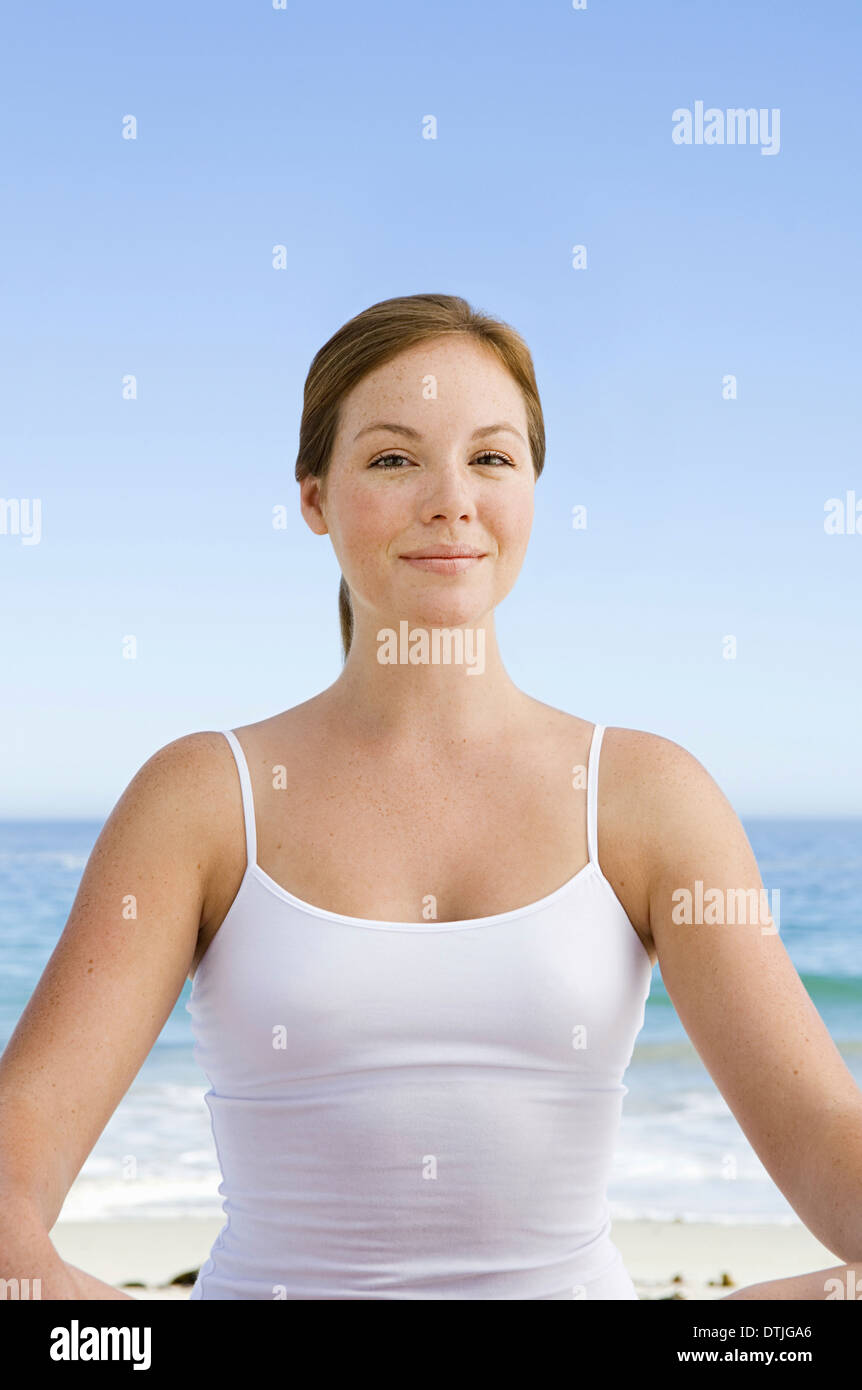 A spa treatment centre A young woman seated in a relaxed pose on the beach  Cape Town South Africa - Stock Image