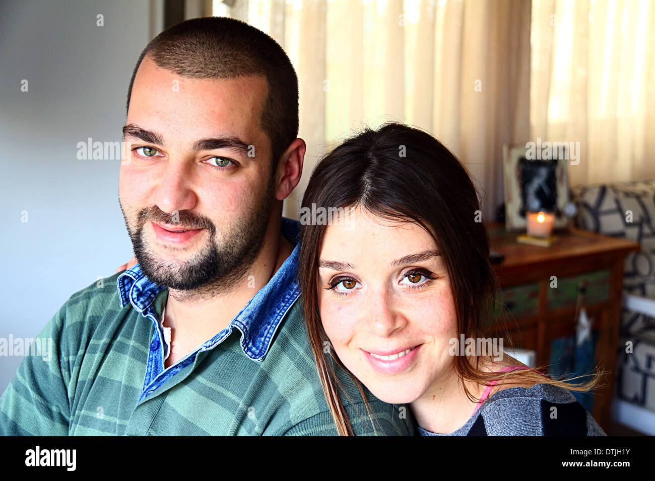 Portrait of Young Married Turkish Couple Smiling At Home - Stock Image