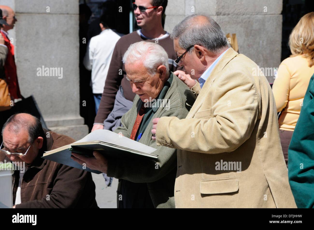 Madrid, Spain. Plaza Mayor. Old men at the Sunday stamp market - Stock Image