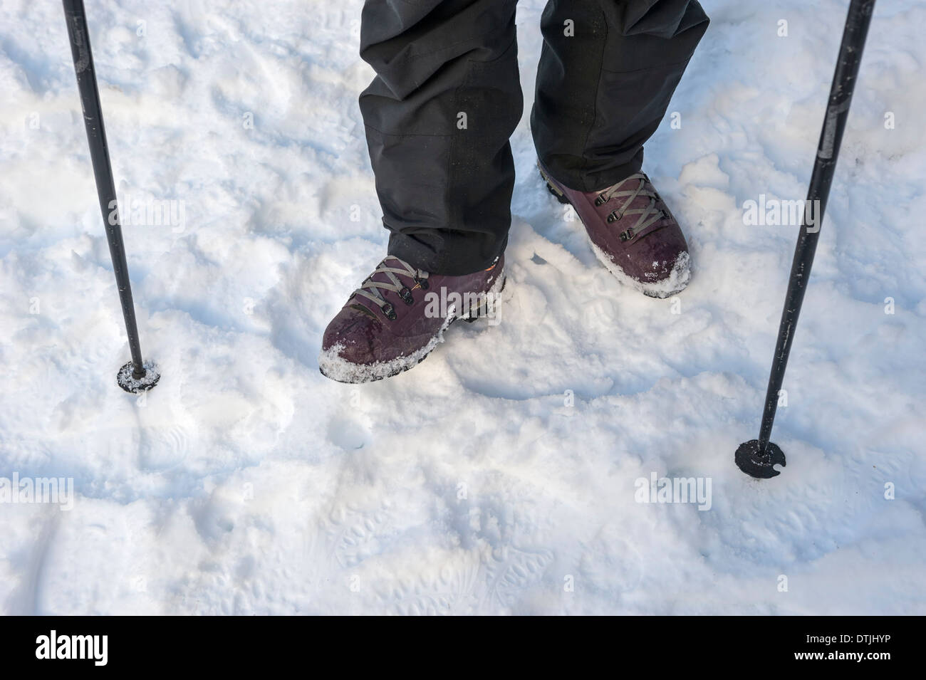 Snow hiking equipment - snow boots and trekking poles - Stock Image