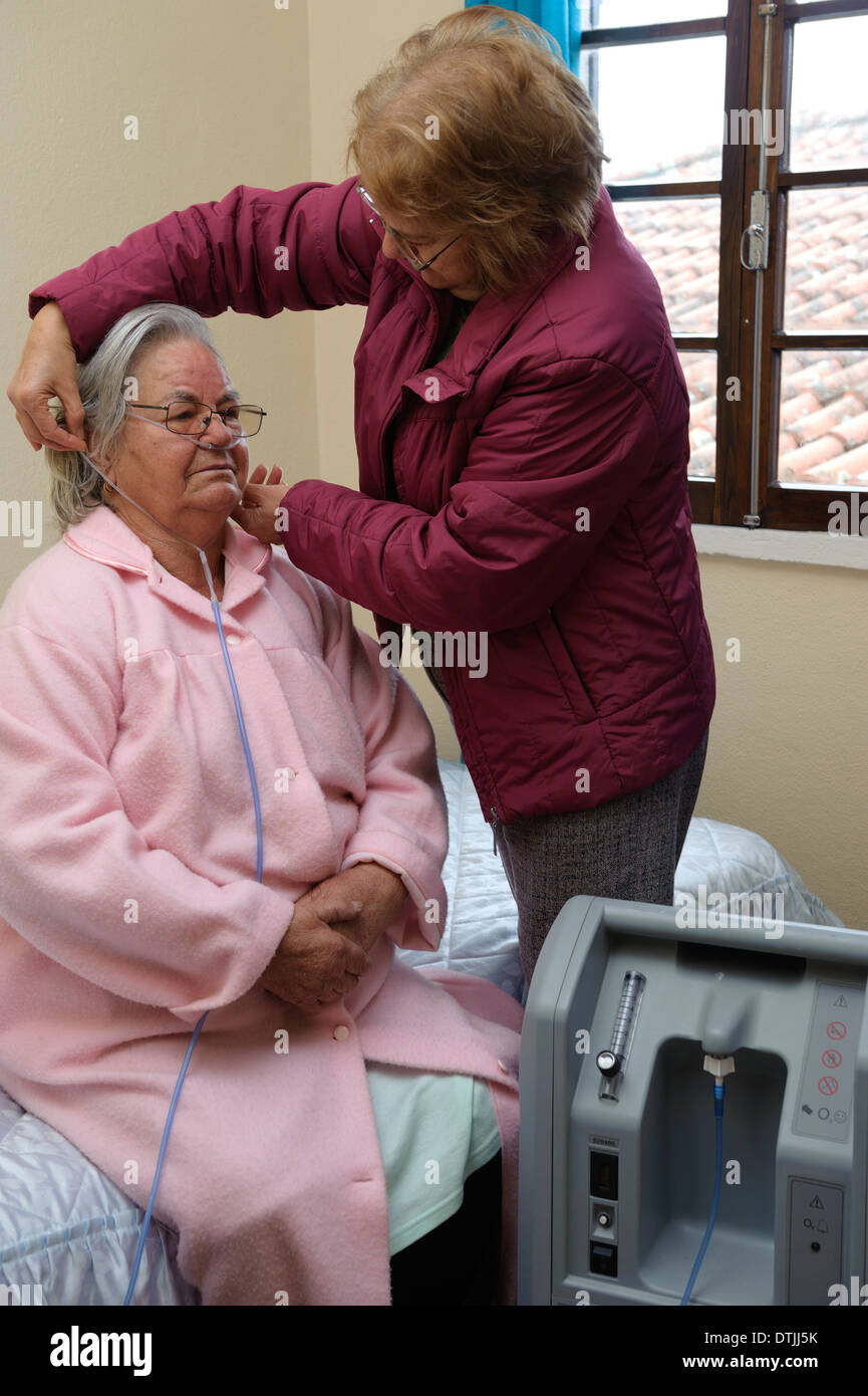 Assistant helping out elderly patient put on nasal cannula to do oxygen therapy with air machine at home - Stock Image