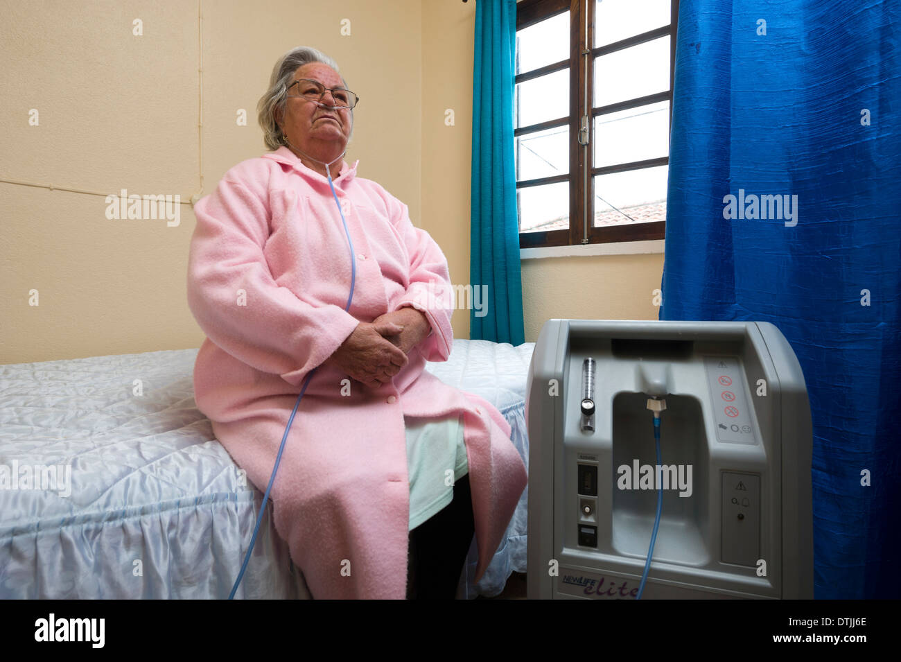 Elderly patient doing oxygen therapy with air machine at home - Stock Image