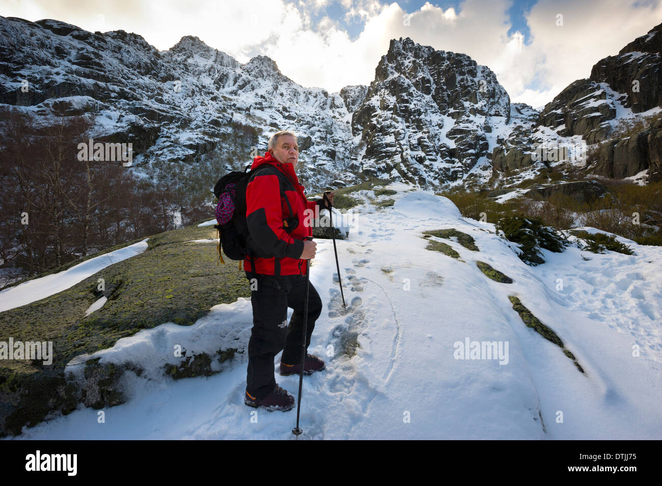Middle aged man climbing a snow covered mountain in the Winter - Stock Image