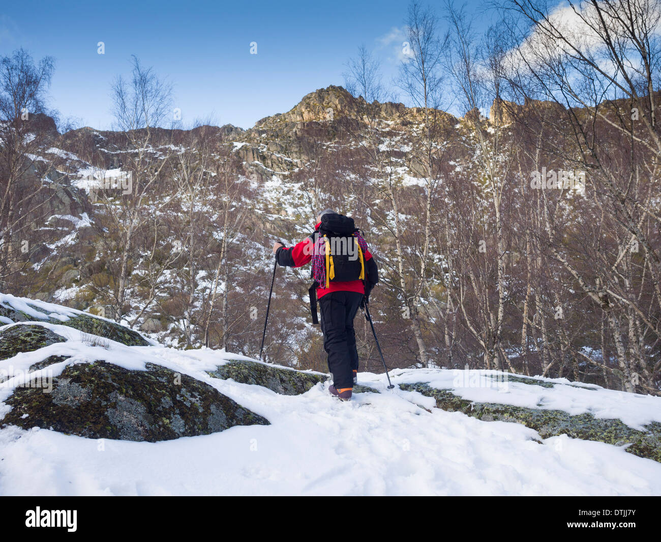 Hiker climbing a mountain covered in snow in the Winter - Stock Image