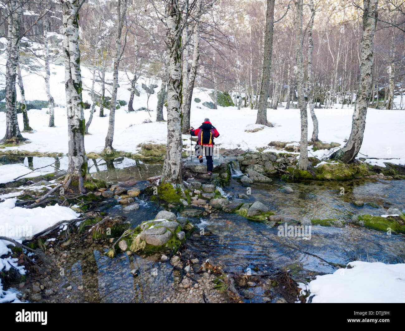 Hiker crossing a river in the Winter - Stock Image