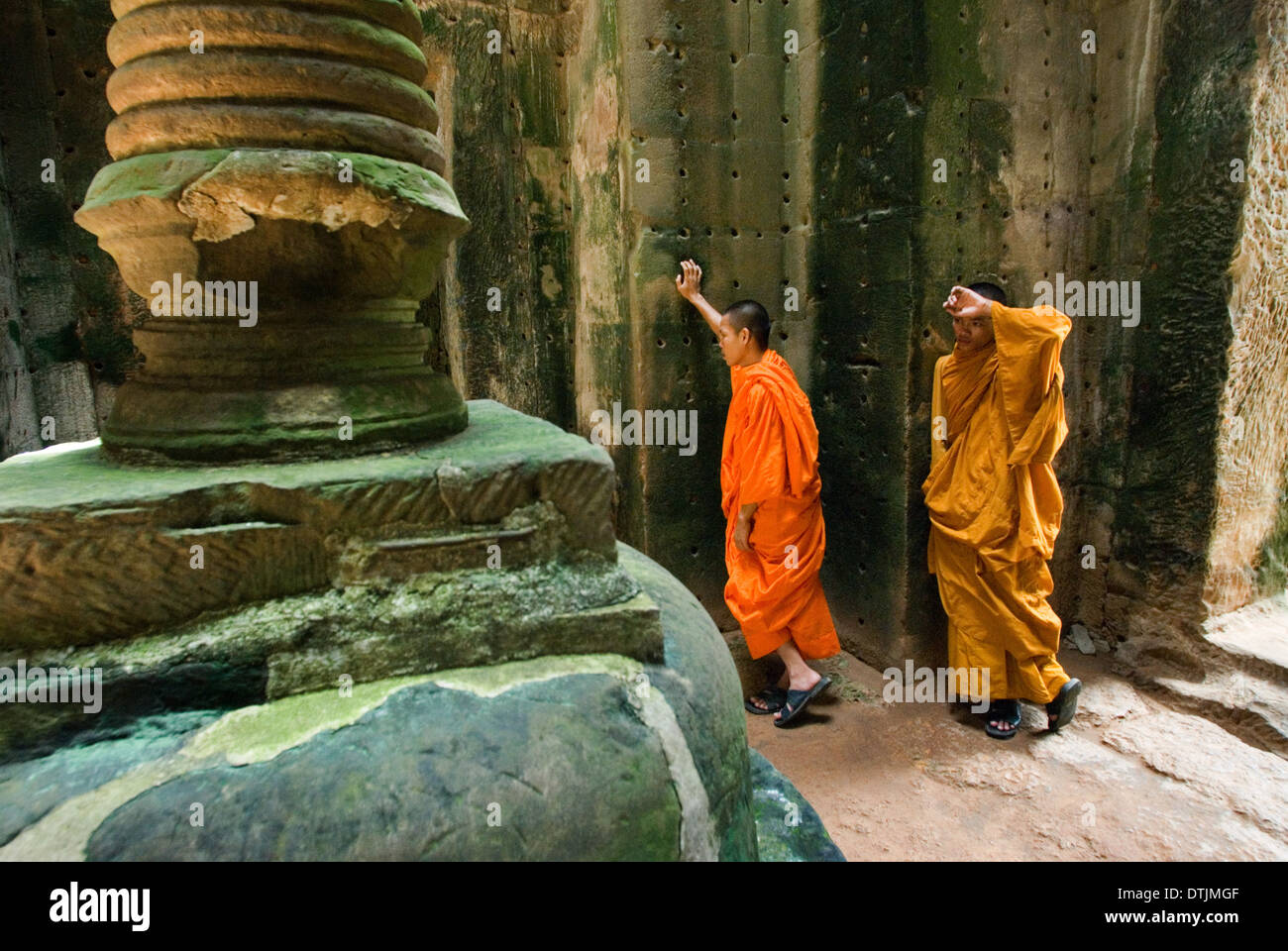 Two Buddhist monks in the inner part of the Temple Preah Khan.  Little is known about the history of Preah Khan. To distinguish - Stock Image