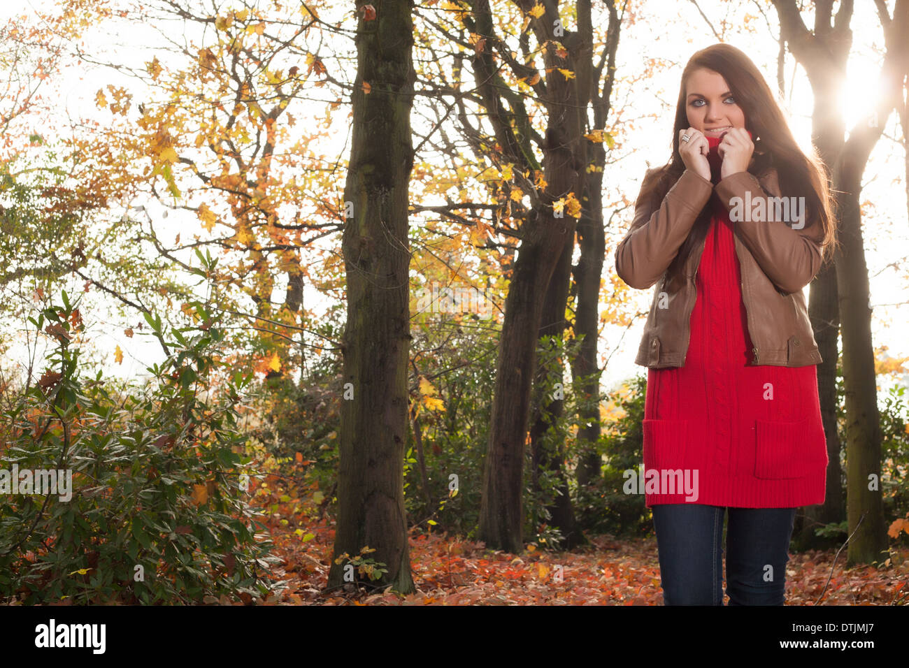 Happy brunette is having a nice time in the park while it's autumn Stock Photo