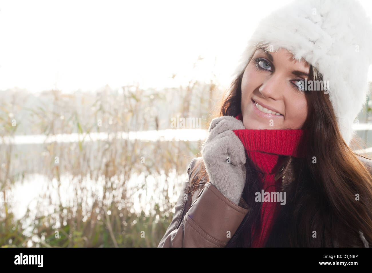 Happy brunette is having a nice time in the park while it's autumn - Stock Image