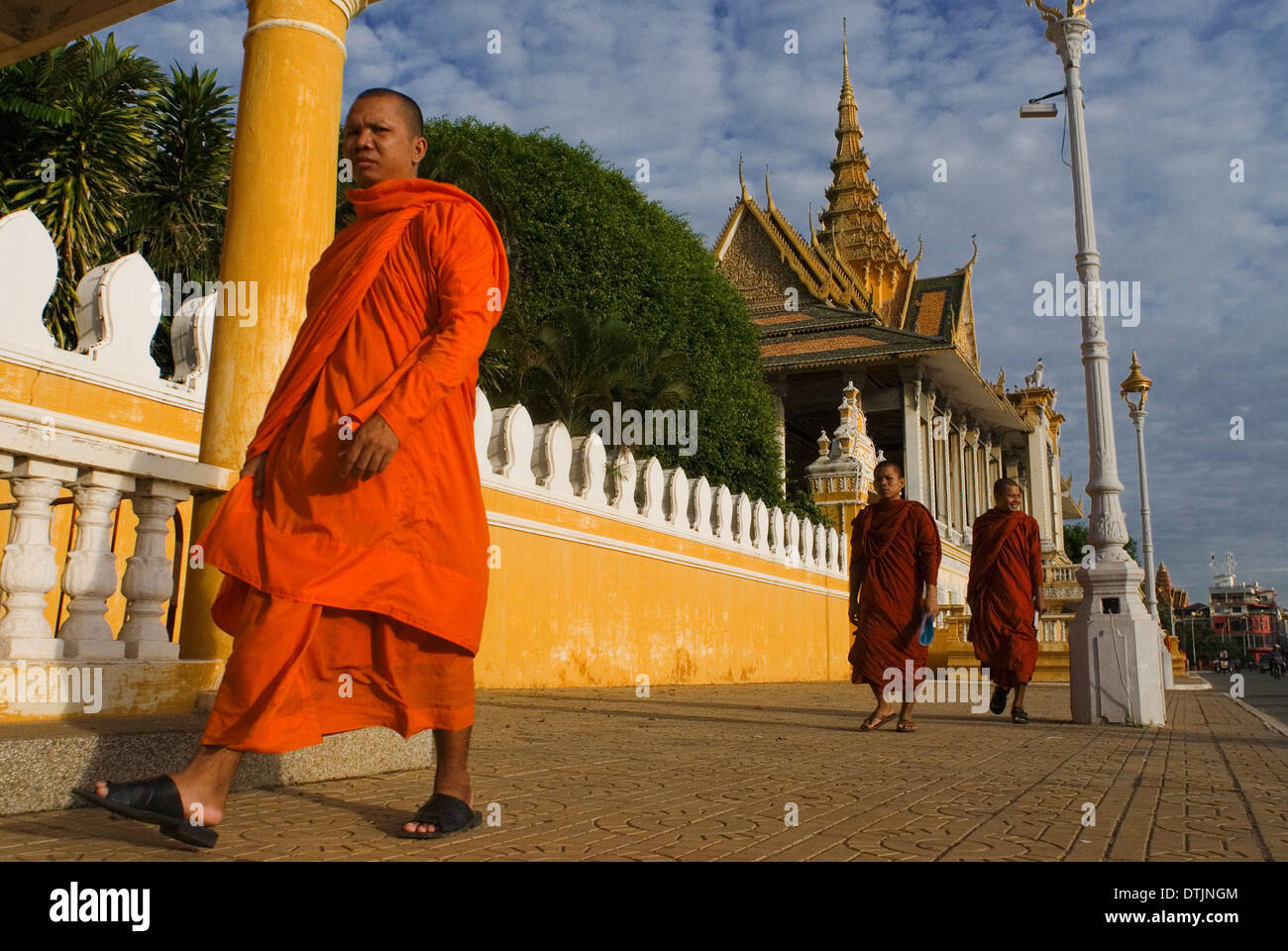 Monks walk outside the Royal Palace. Phnom Penh. Gleaming in gold, the Royal Palace is one of Phnom Penh?s most splendid archite - Stock Image