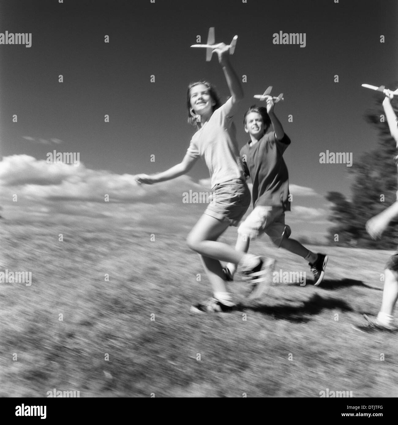 Children running with paper airplanes on the Grand Allee at Castle Hill, Ipswich, MA - Stock Image