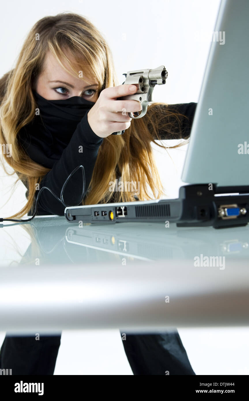 woman with a mask pointing a gun on the notebook (model-released) - Stock Image