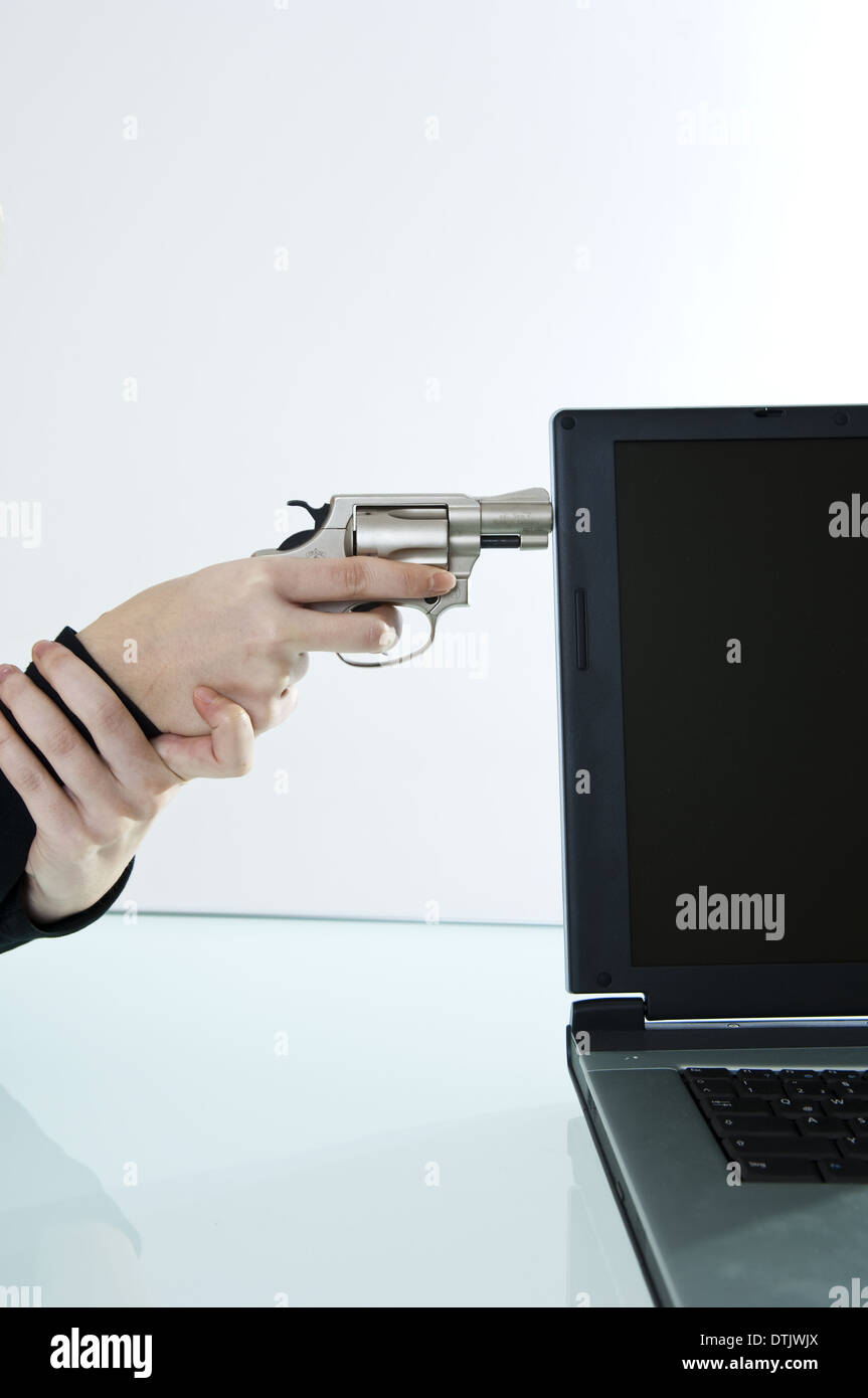 woman pointing on a notebook with a gun (model-released) - Stock Image