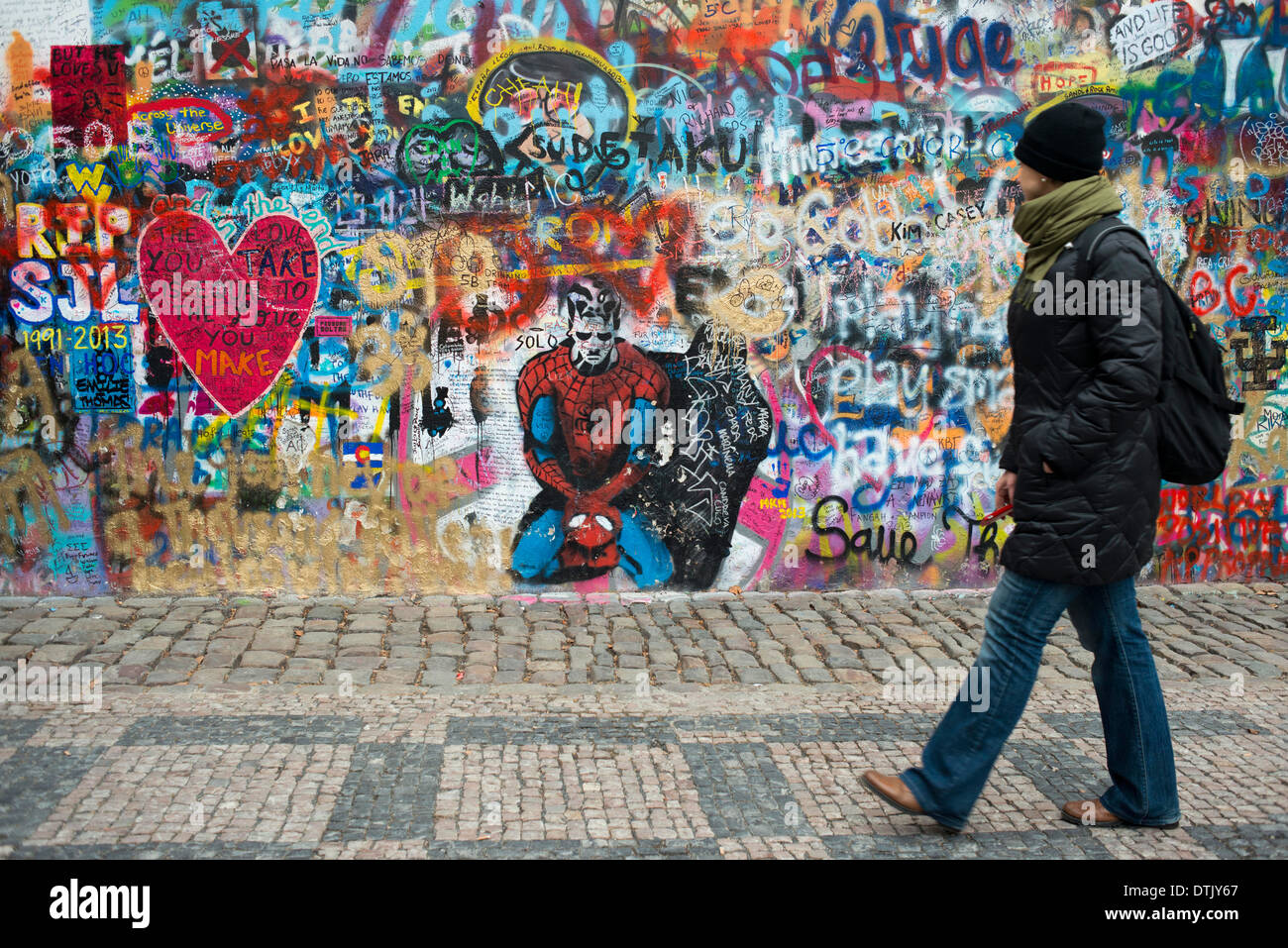 A girl walks past the John Lennon Wall in Prague center . The John Lennon Wall is a wall, which once was one most of which could - Stock Image