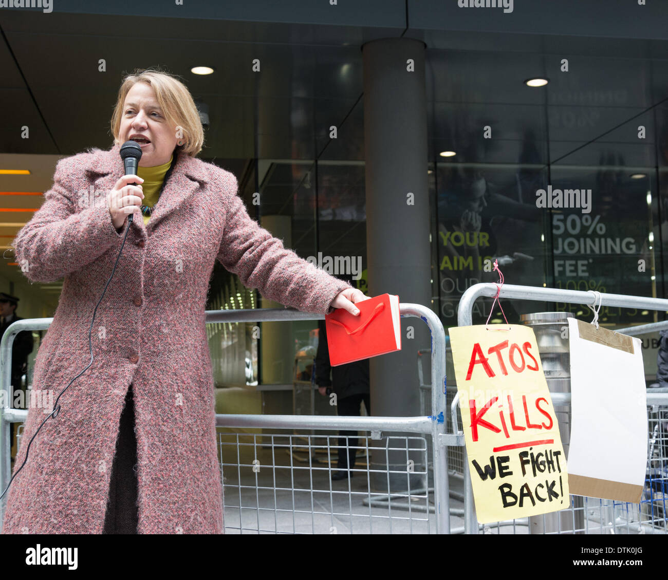 ATOS headquarters, London, UK, 19th February, 2014. Leader of the Green Party Natalie Bennett speaks outside ATOS head office in London to protest the company's implementation of Work Capability Assessments. Protesters say that ATOS workers with little or no medical knowledge make poor decisions which lead to people losing their sickness benefits, and demand that a qualified medical doctor, ideally the GP who regularly sees and treats the sick or disabled person in question, is the only person able to decide if an individual is fit for work. Credit:  Patricia Phillips/Alamy Live News - Stock Image