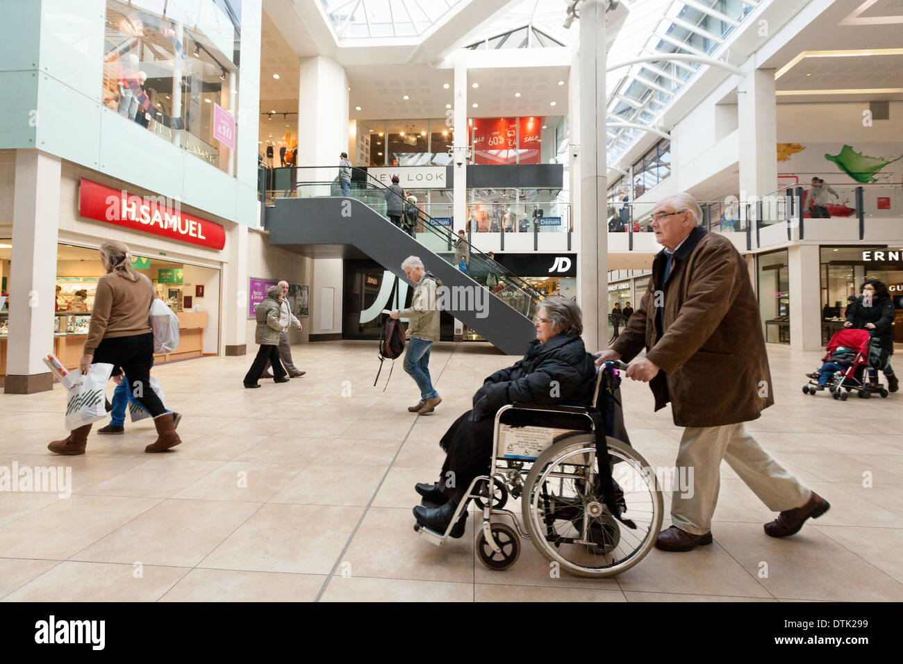 Disabled access to shops - An elderly couple with a disabled person in a wheelchair in a shopping mall, England UK - Stock Image