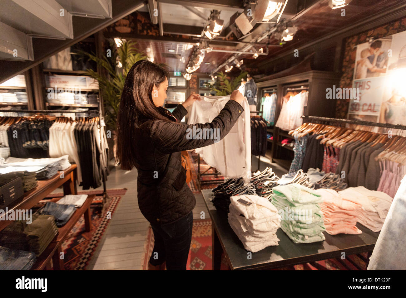 A young woman shopping and buying clothes in the Hollister ...