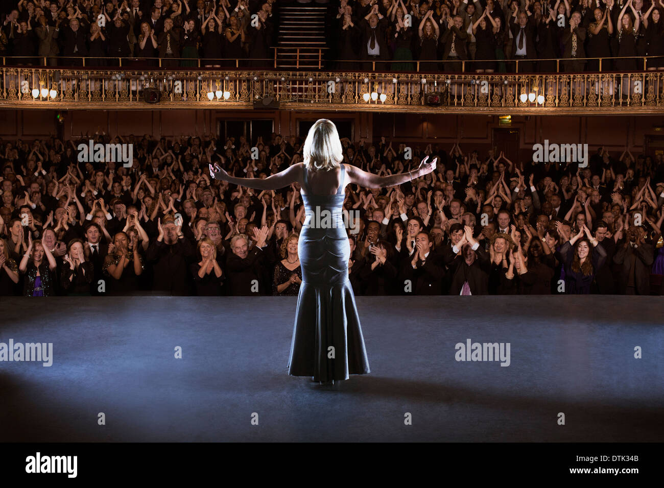 Performer standing with arms outstretched on stage in theater Stock Photo