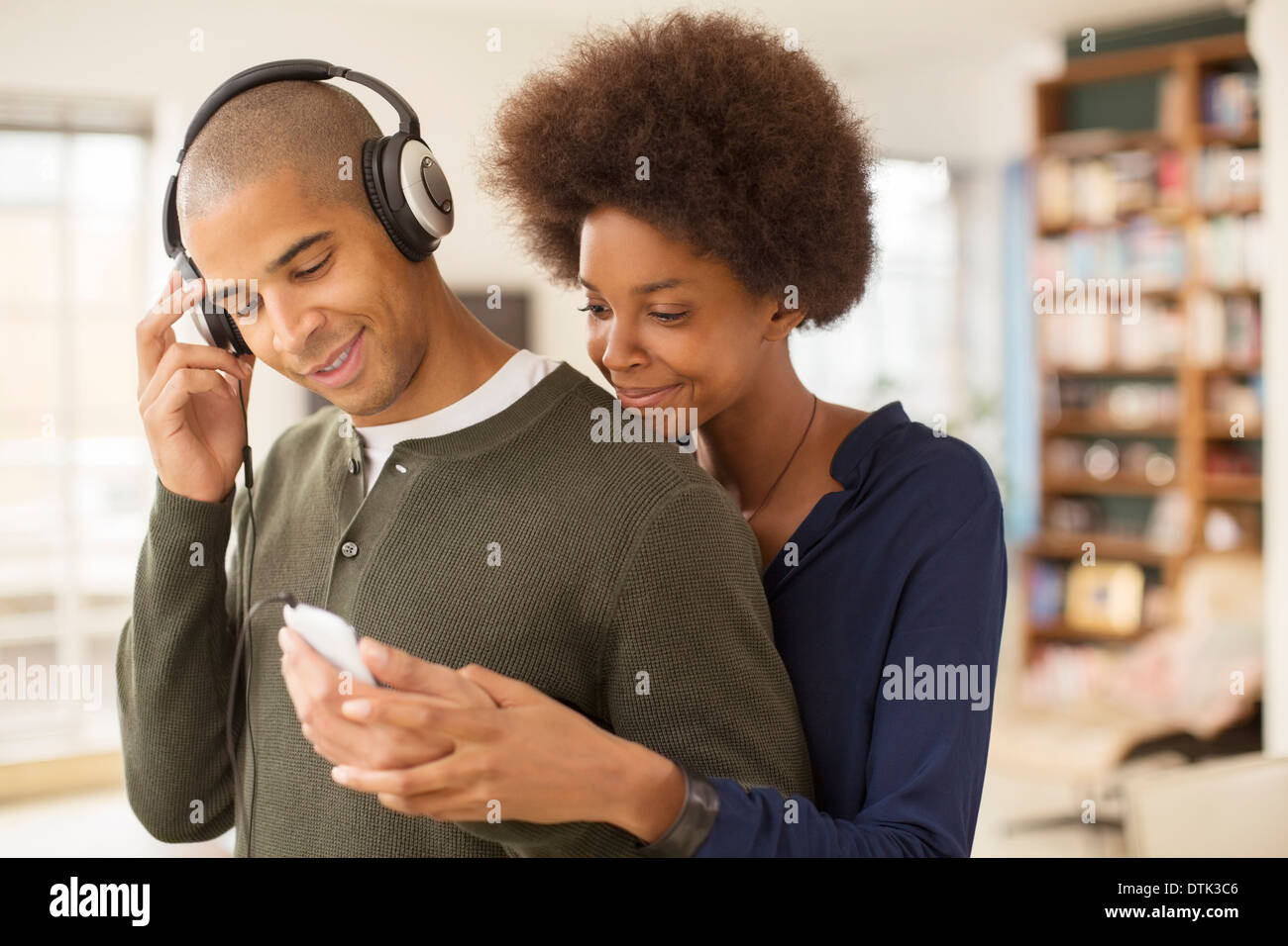 Couple using mp3 player together - Stock Image
